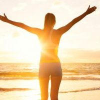 Happy successful fitness woman raising arms to the sky at sunset. Success, celebrating goals and achievement. Healthy Active Lifestyle.